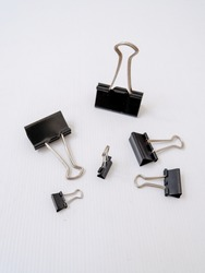 Isolated black binder clips (or foldback clips office, paper clip) in different sizes with white background.