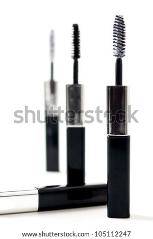 Isolated black mascara with brush laying on white background