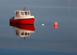 Isolated boat and buoy in calm water