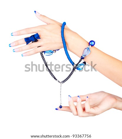 isolated body part shot of beautiful young woman's manicured hands with fancy blue beads on white