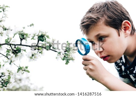 Isolated boy looking at flower through magnifier. Charming schoolboy exploring nature. Kid discovering spring cherry blossoms with magnifying glass. Young biologist, curious child outdoor activity #1416287516