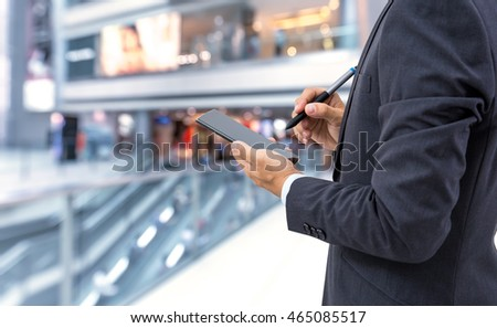 isolated business man hold the smartphone on shopping mall background #465085517