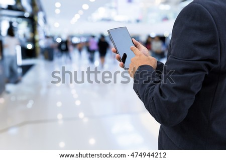 isolated business man hold the smartphone on shopping mall background  - Shutterstock ID 474944212