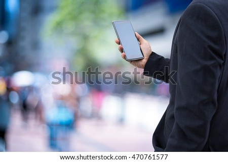 isolated business man hold the smartphone on the street  - Shutterstock ID 470761577