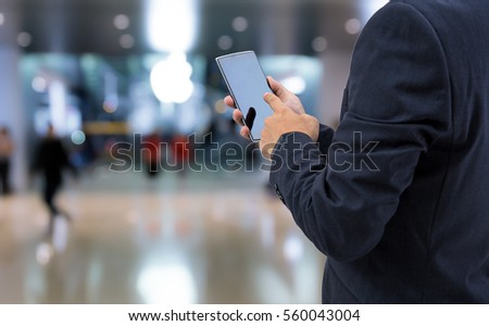 isolated business man holds the smartphone on shopping mall background  - Shutterstock ID 560043004