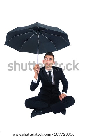 Isolated business man with umbrella sitting down - stock photo