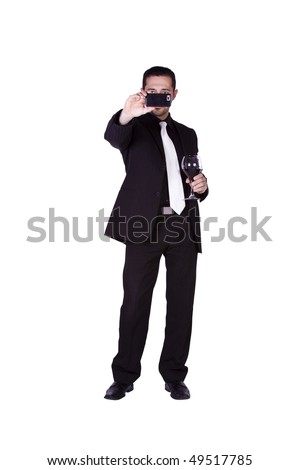 Isolated businessman celebrating with a glass of drink while sending a picture message on his cell phone