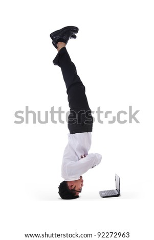 Isolated businessman headstand with laptop on white background
