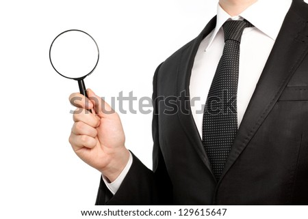 Isolated businessman in a suit and tie holding a magnifying glass
