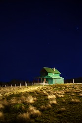 Isolated cabin on hill top at night with clear blue sky