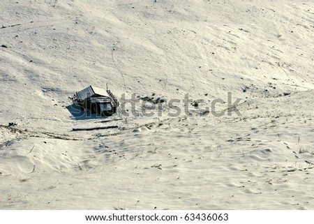 Isolated cabin on the plains of snow - aerial view