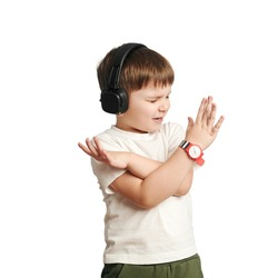 isolated child in headphones listens to music and sings on white background. happy little boy. cross arms.