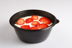 isolated close up corner view shot of a delicious white rice milk porridge with red strawberry fruit slices on top in a black plastic bowl on a white background