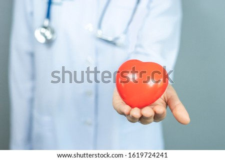 isolated close up of asian female doctor holding a red love heart onto her palms, representing checkup, diagnosing, health care, medical care, hospital care, wearing white lab coat and a stethoscope