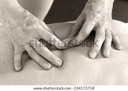 Isolated close-up of the hands of the masseur - female on man's back during a session, studio #234173758