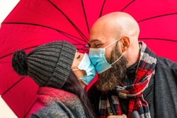 isolated close up portrait of a young adult couple kissing each other with passion wearing protective face mask. hipster man and caucasian woman wearing warm winter clothes in love. new normal life