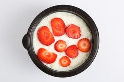 isolated close up top view flat lay shot of a delicious white rice milk porridge with red strawberry fruit slices on top, in a black plastic bowl, on a white background