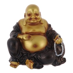 Isolated close up view of souvenir statuette of a golden Buddha on white background.
