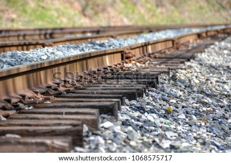 Isolated closeup of railroad track.  Low angle view features a stone ballast bed, the wooden railway sleeper sections, rail te plate, steel rail and spikes.
