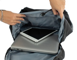 Isolated closeup studio shot of female hands opening canvas fabric backpack putting touchscreen tablet and laptop computer notebook inside shockproof elastic compartment pocket on white background.