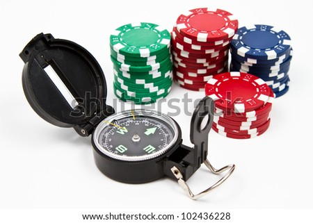Isolated compass and red, green and blue chips over withe table - stock photo