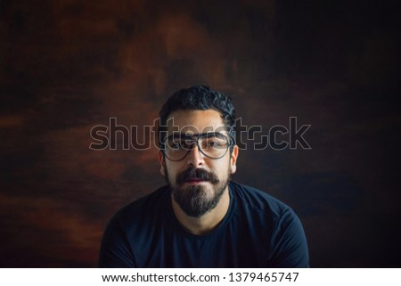 Isolated confident  hispanic latin arab indian caucasian middle eastern bearded white man, intellectual nerdy hipster guy, with eyeglasses,in a wooden brown background and plenty of copy-space