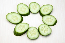 Isolated cucumbers. One whole cucumber and slices of cucumber isolated on white background