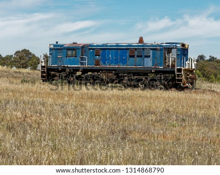 Isolated dark Blue Diesel Electric  48Class Locomotive in a field of dry yellow grass,  Junee, New South Wales,  Australia. #1314868790