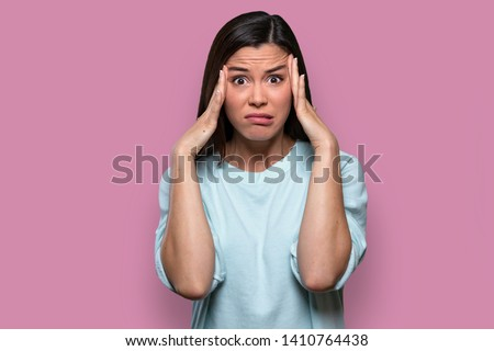 Isolated facial expression of a worried, concerned, fearful, regretful woman, expressing distress and inner conflict, pink background #1410764438