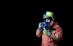 Isolated firefighter sadly putting on protective gear so he can breathe. Black background.