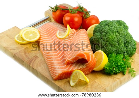 Isolated fresh raw red fish with lemon, broccoli, greenery and tomatoes on the wooden cutting board