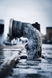 Isolated frozen water supply hydrant  at a sidewalk