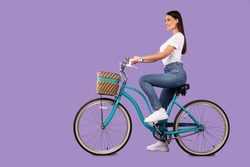 Isolated Full Length Portrait Of Young Woman Riding Bike, Side View, Copy Space, Isolated Over Pastel Purple Studio Wall