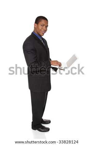 Isolated full length studio shot of a confident businessman looking at the camera while holding a laptop computer.