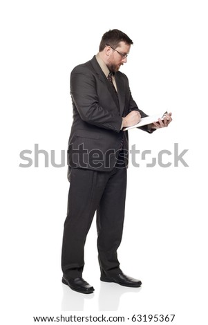 Isolated full length studio shot of the side view of a businessman writing on a clipboard.