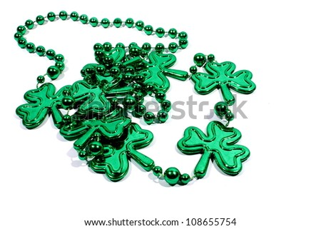 Isolated green mardi gras necklace with three leaf clovers.