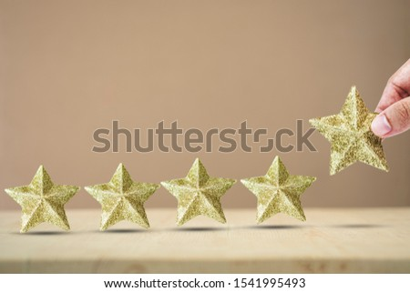 Isolated Hand putting luxury golden star for increase star unit from 4 pieces to 5 pieces on wooden table. Excellent business service rating concept.