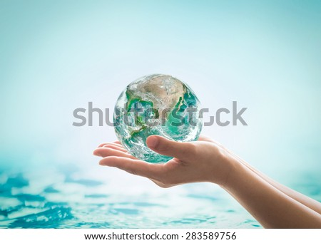 Isolated hands holding green planet on turquoise green water background : World ocean day and hydrography concept: Elements of this image furnished by NASA