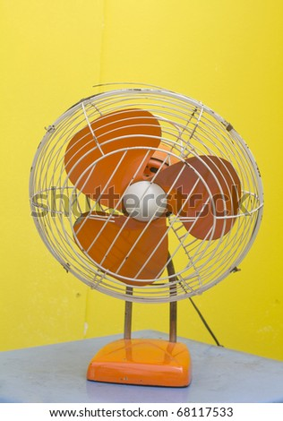 Isolated image of a fan working against a yellow background