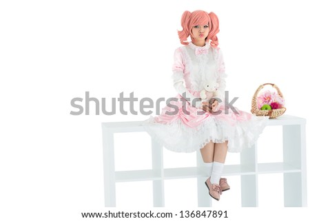 Isolated image of a kawaii girl sitting on a white shelve stand and pouting her lips