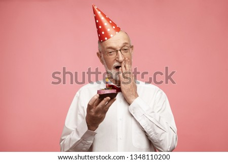 Isolated image of handsome emotional unshaven Caucasian male wearing glasses, white shirt, bow tie and holiday hat covering his opened mouth, having amazed look, holding birthday cupcake with candle