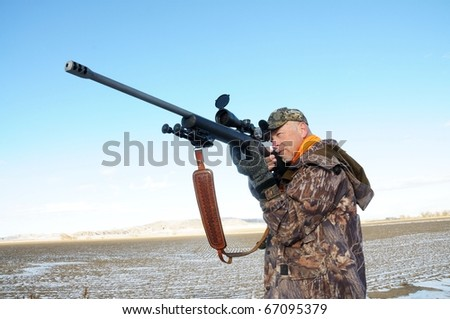 Isolated image of hunter with rifle.  Image took place in Wyoming while hunting big-game.