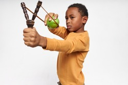 Isolated image of serious concentrated little black boy holding Y-shaped stick with elastic, shooting green apple, having focused facial expression. Accurate African child playing with slingshot