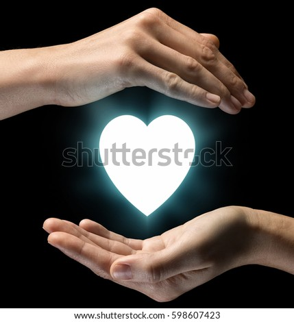 Isolated image of two hands on black background. Heart  icon in the center, as a symbol of love and care. Concept of care of love and care. #598607423