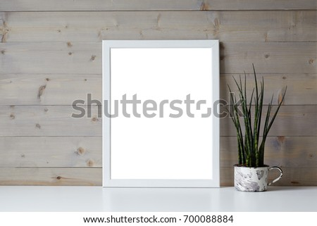 Isolated interior shot of decorative fresh green plant in pot and blank photo frame with copy space for your picture, content or promotional information resting on white shelf at wooden wall.