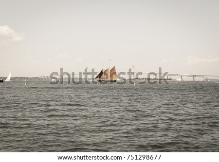 Isolated large sailing sail boat. Large ship in ocean. Roaring waves. Bridge background. Abstract color background.