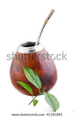 Isolated Leather Mate Cup with Straw and yerba green leafs .