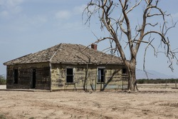 Isolated lonely weathered worn old empty abandoned wooden nostalgic farm homestead in bleak dry arid tree landscape