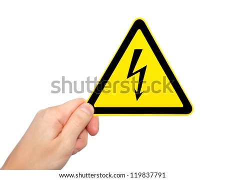 isolated male hand holding yellow sign of danger high voltage symbol with lightning