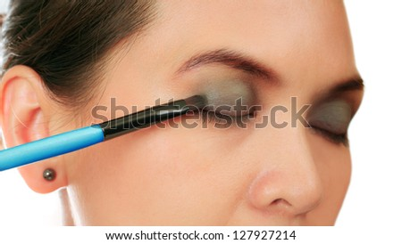 Isolated middle age woman with a make up brush